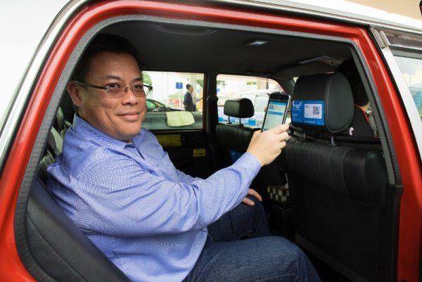 TNG行政總裁江慶恩先生示範以TNG電子錢包支付的士車資。